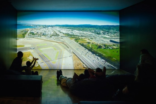 Visitors take an aerial tour of the shoreline of the San Francisco Bay Area, with a video projection commissioned by the Museum for its current exhibition, Above and Below: Stories From Our Changing Bay and created by the Center for Land Use Interpretation. The shore around the bay has been altered by humans and nature alike, and viewing it from above can consider the Bay's history and our relationship to our environment. Photo: Shaun Roberts. Courtesy of Oakland Museum of California.