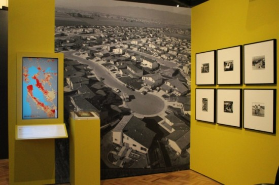 A photograph from Bill Owens' Suburbia series illustrates the changes brought by the new Bay Bridge when it was completed in the 1930s; a digital map showing the change in population density throughout the Bay Area further illuminates how the ease of automobile travel enabled development. Image courtesy of Oakland Museum of California.