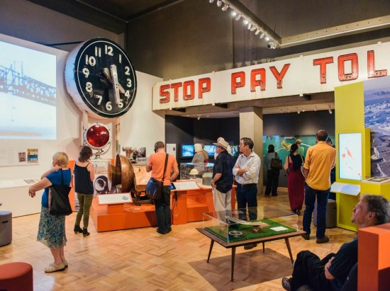 """Conservators worked with CalTrans to conserve and mount significant artifacts like this Art Deco clock and """"Stop Pay Toll"""" sign which once greeted passing cars on the Bay Bridge. A dynamic map of Bay Area development in the 20th century, created in conjunction with Stanford's Spatial History Project, along with photographs of suburbia by Bill Owens, conveys the impact of the 1936 bridge on land use around the Bay."""