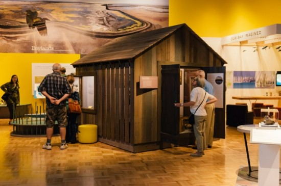 """Drawbridge: A Hunting Community - The exhibition weaves in quirky, forgotten stories, illuminating the relationships we once had with the Bay and have lost. Here, a stage-set """"hunting shack"""" tells the story of the town of Drawbridge, now a ghost town in the marshes of the South Bay. Visitors open doors and windows onto vignettes of the duck hunters who made their living harvesting the natural world of the Bay 100 years ago."""